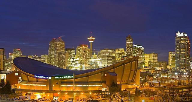 The Saddledome with Calgary Tower and the city skyline in the background at dusk, Calgary, Alberta, Canada (© Rolf Hicker)