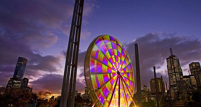 Colourful ferris wheel in Birrarung Marr park and the city skyline at dusk, Melbourne, Victoria