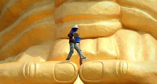 A worker walks across the Luang Pu Thuad statue near Ayutthaya, Thailand