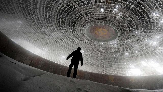 A man walks inside the crumbling skeleton of the House of the Bulgarian Communist Party on Mount Buzludzha, Bulgaria (© Dimitar Dilkoff/Getty Images)