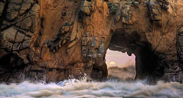 Waves and sea spray through a sea arch at Pfeiffer Beach in Big Sur, California
