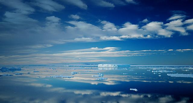 Antarctic iceberg and cloud landscape reflecting in totally calm waters near Ross Island, Antarctica