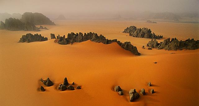 Pinnacles of sandstone among orange dunes of the Karnasai Valley, Chad