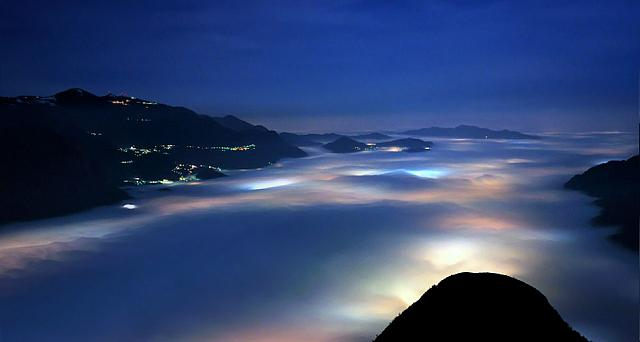 A layer of low clouds covers Olginate Lake and the villages around its banks, near Lake Como Italy