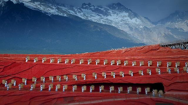 Folk dance performance in front of Jade Dragon Snow Mountain in Lijiang, Yunnan, China (© Bob Krist)
