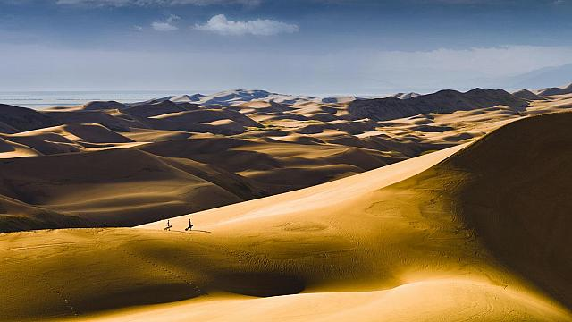 Sandboarders hiking up dunes for another ride, Great Sand Dunes National Park, Colorado (© Glenn Oakley)
