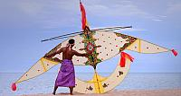 A Malaysian man holds a traditional handmade kite