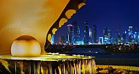 The pearl monument in the Corniche neighborhood of Doha, Qatar, illiminated at night with the new high-rises of West Bay in the