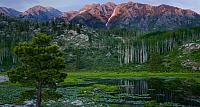 The peaks of the San Juan Mountains, part of the Rocky Mountains, rise above a beaver pond  in southwest Colorado