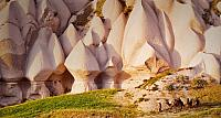 Eroded rock formations and camels in Uchisar, Cappadocia, Turkey