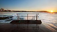 Sunrise on Bondi Beach in Sydney, Australia with a handrail in foreground (© Pawel Papis)