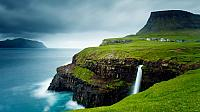Village of Gásadalur below Heinanova mountain, with waterfall cascading over cliff into the Atlantic Ocean, Faroe Islands (© Kimberley Coole/Lonely Planet)