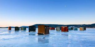 Ice fishing huts on frozen lake in New York State, USA (© Dermot Conlan/Corbis)