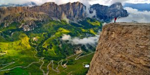Trekker on the Sella Group mountain chain, looking down on the road from Badia Valley to Gardena Pass, Dolomites, South Tyrol, Italy (© SIME/eStock Photo)
