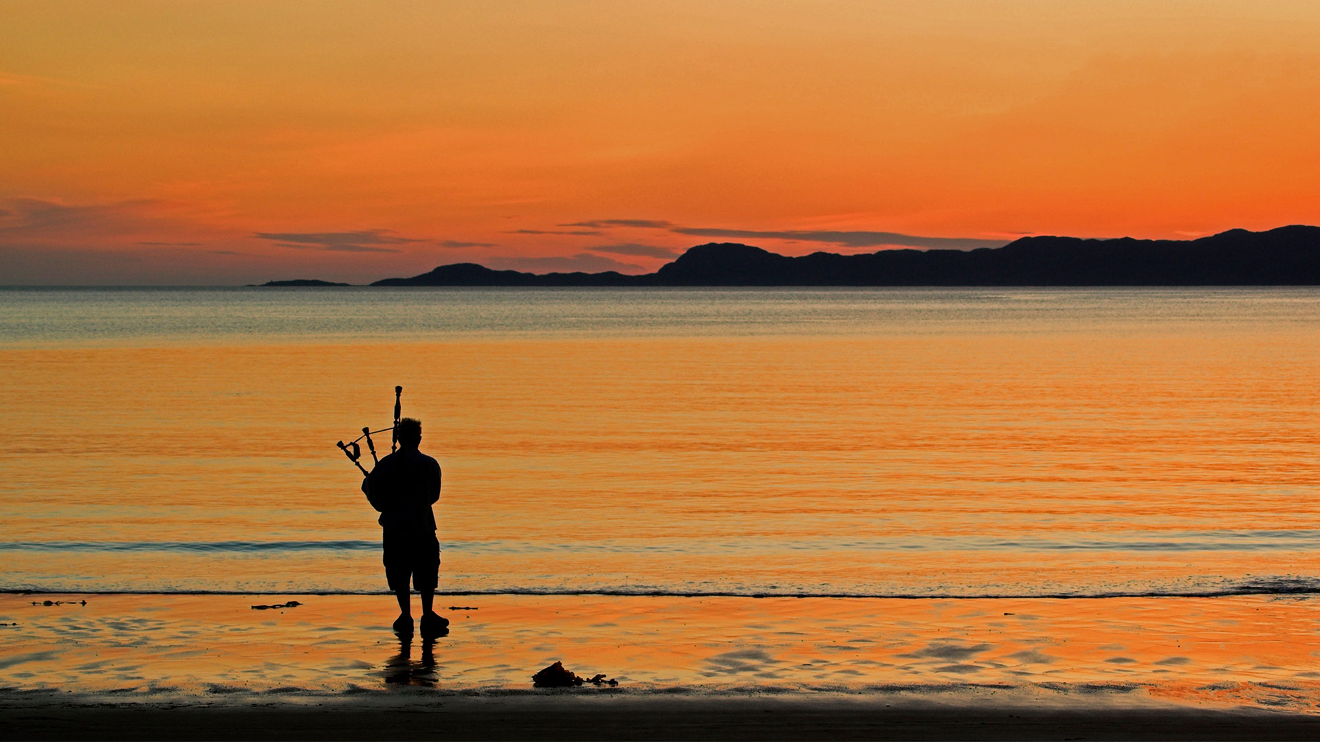 A bagpiper on Arisaig beach in Scotland (© ColsTravel/Alamy)
