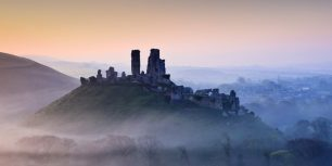 Corfe Castle shrouded in mist at sunrise in Dorset, England (© Mark Bauer/LOOP IMAGES/Loop Images/Corbis)